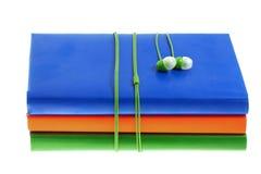 Hełmofony i sterta stubarwne książki na białym tle Obraz Royalty Free