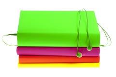 Hełmofony i sterta stubarwne książki na białym tle Zdjęcie Stock