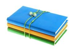 Hełmofony i sterta stubarwne książki na białym tle Zdjęcia Royalty Free