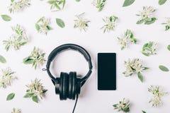 Hełmofony i telefon komórkowy na białym stole Fotografia Royalty Free