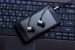 Hełmofony i telefon komórkowy przy klawiaturą Obraz Royalty Free