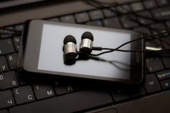 Hełmofony i telefon komórkowy przy klawiaturą Fotografia Royalty Free