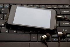 Hełmofony i telefon komórkowy przy klawiaturą Obraz Stock