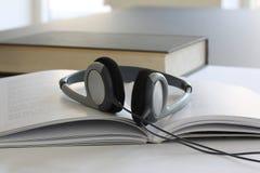 Hełmofony kłama na otwartej książce z bliska fotografia stock
