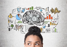 Head of African American woman, brain with gears. Close up of a head of an African American woman standing near a concrete wall with a brain sketch with gears Royalty Free Stock Image