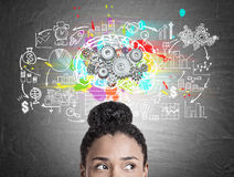 Head of African American woman, gears and brain. Close up of a head of an African American woman standing near a blackboard with a brain sketch with gears and a Stock Image