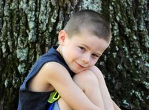Head Against Knees with a Grin. Little boy sits besides a tree outdoors. He leans his head against his knees as he enjoys being outside royalty free stock photo