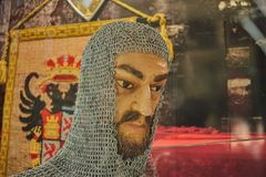 Head of ancient man with beard covered by mesh of rings for protection with a old pennant in the background in Toledo, Spain stock photography