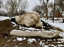 The Head and Arm of the Awaking Muse. This is a Winter picture of the head and arm of a piece of public art titled: Awaking Muse, on exhibit in the Chicago stock images