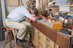 Head on arms on workbench. Older man with head on arms in his workshop surrounded by tools and equipment Royalty Free Stock Photography