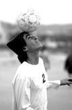 Head balance. Boy balancing soccer ball above his head. Black and white Stock Photo