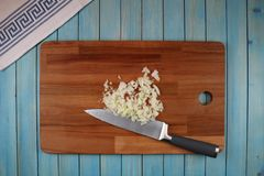 Head of black onion on a wooden board for cutting vegetables stock image