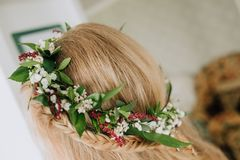 Head blond girl wreath flowers pigtail room. Head of a blond girl with a wreath of flowers and a pigtail inside the room Stock Images
