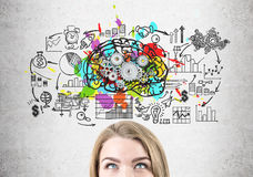 Head of blond woman, brain with gears. Close up of a head of a woman standing near a concrete wall with a brain sketch with gears and a startup drawing Stock Photography