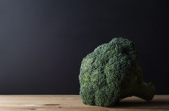 Head of Broccoli on Wooden Table. A head of dark green broccoli with stalk intact, on wooden planked kitchen table against black chalkboard background.  Moody Stock Image