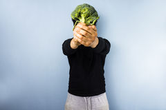 Head of broccoli. Young man holding a head of broccoli up in front of his face Stock Photography