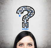 A head of brunette lady who is thinking about problem solving. A question mark as a maze. Concrete background Royalty Free Stock Images