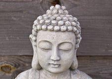 Head of Buddha on grey wooden background. Stock Photo