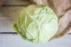 Head of cabbage on sackcloth on white wooden table, top view Royalty Free Stock Image
