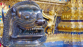 Head of cambodian brass lion in wat phra kaew. , bangkok, Thailand. Brass lion sculptures both sides of the main entrance guards the Emerald Buddha. Located at Royalty Free Stock Image