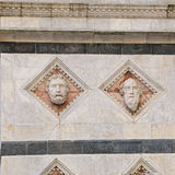 Head carved in marble on the facade of the Siena Baptistery Royalty Free Stock Photography