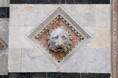 Head carved in marble on the facade of the Siena Baptistery Royalty Free Stock Photo