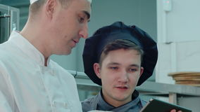 Head chef explaining something to cook trainee in hat using digital tablet stock footage