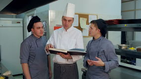 Head chef holding recipe book and discussing something with his trainees stock video footage