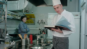 Head chef looking for a recipe in the book for cook trainee to prepare stock video footage