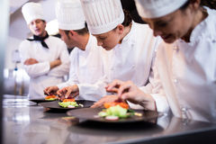 Head chef overlooking other chef preparing dish. In the kitchen Stock Photo