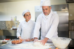 Head chef showing happy trainee how to prepare dough Royalty Free Stock Photography