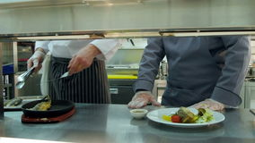 Head chef showing his assistant how to serve fish on an iron platter stock footage