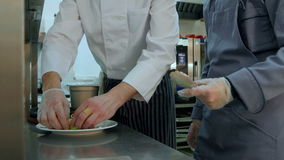 Head chef showing his assistant how to serve the salad stock video footage
