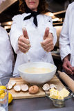 Head chef showing thumbs up while preparing dough Stock Image