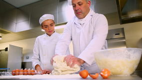 Head chef showing trainee how to prepare dough Royalty Free Stock Photography
