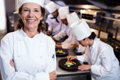 Head chef smiling in busy kitchen Stock Image