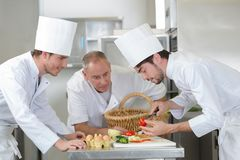 Head chef teaching colleagues how to slice vegetables stock photo