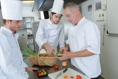 Head chef teaching colleagues how to slice vegetables stock photos