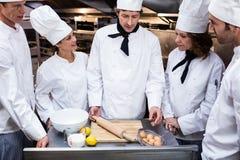 Head chef teaching his team to prepare a dough. Head chef in commercial kitchen teaching his team to prepare a dough stock photography