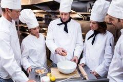 Head chef teaching his team to prepare a dough. Head chef in commercial kitchen teaching his team to prepare a dough stock photo