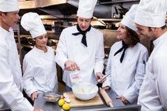 Head chef teaching his team to prepare a dough. Head chef in commercial kitchen teaching his team to prepare a dough stock photos