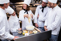 Head chef teaching his team to prepare a dough stock images