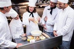 Head chef teaching his team to prepare a dough. Head chef in commercial kitchen teaching his team to prepare a dough royalty free stock photography