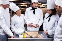 Head chef teaching his team to prepare a dough. Head chef in commercial kitchen teaching his team to prepare a dough royalty free stock image