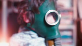 The head of the child is wearing a gas mask
