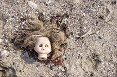 Head of children's doll on the beach trash Stock Photos