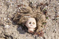 Head of children's doll on the beach trash Royalty Free Stock Photography