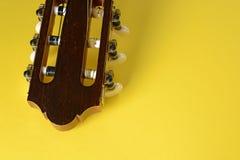 Head closeup för gitarr på guling Arkivfoto