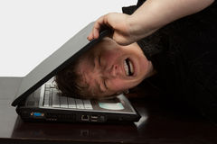 Head in computer. Head of a blond woman with painful facial expression inside of a laptop computer stock photography