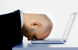 Head on computer. A closeup, studio view of a man with his head on the keyboard of a laptop computer.  Possible themes: dumb mistake, discouraged, overwhelmed Stock Photography